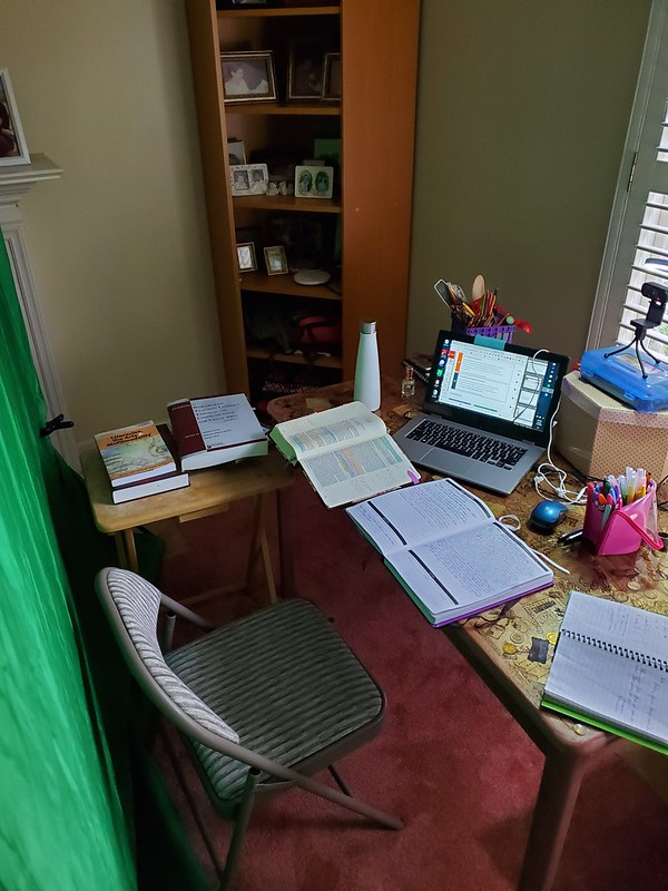 Home workspace. Green screen, table with laptop, camera, pens and pencils, and books.